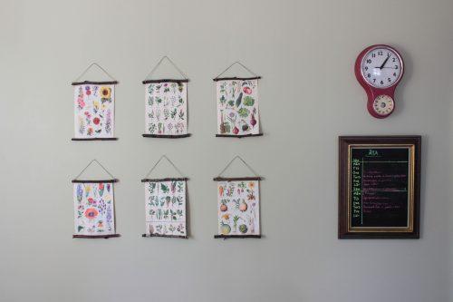 På den kryddgröna väggen hänger DIY skolplanscher med blommor och grönsaker, en röd klocka samt en menytavla.
