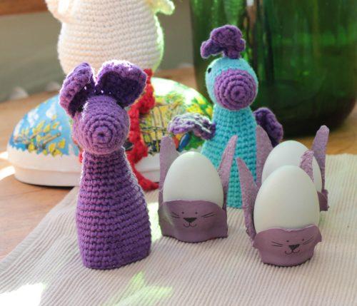 Äggkoppar av äggkartonger formade och målade som kaniner och två virkade äggvärmare.