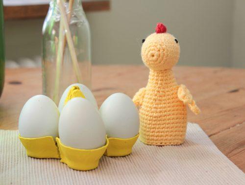 Ägg i hemgjorda gula äggkoppar och en äggvärmande höna.