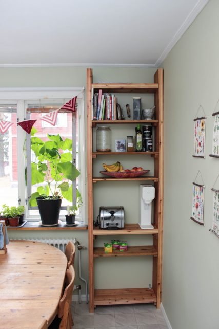 Hemsnickrad bokhylla av tjocka golvplank i kök.
