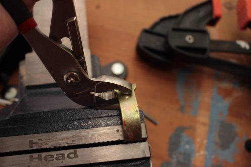 Böjer en fast nyckel med en tång.