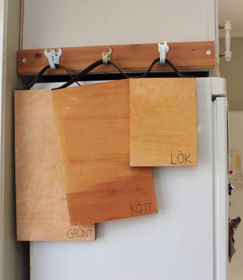 Skärbrädor med läderhandtag hänger på krokar på väggen.