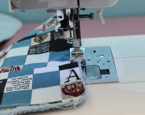 En symaskin syr en stickningssöm i kanten på torkdukarna.