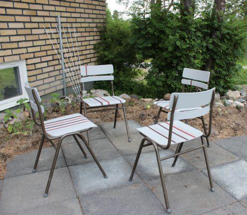 Fyra stolar står på en uteplats av betongsten. Stolarna är inne-stolar som gjorts om till ute-stolar.
