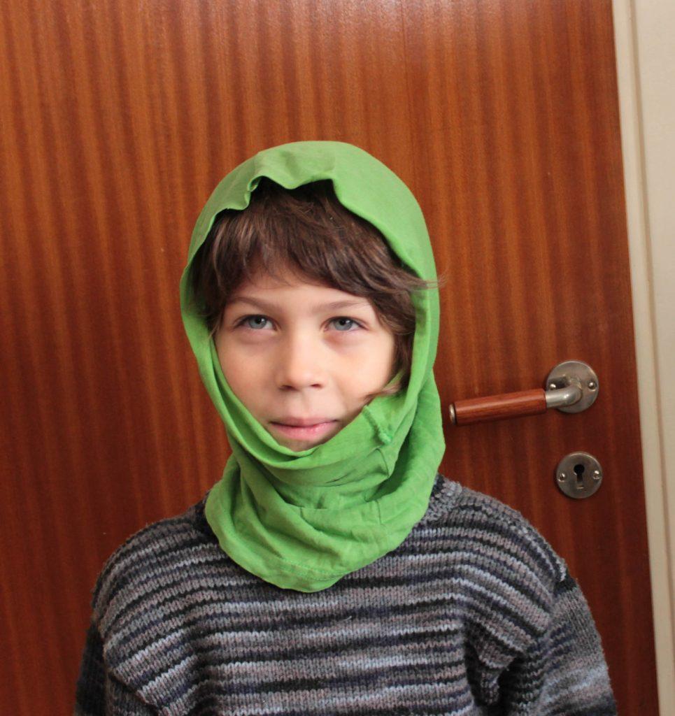 Pojke med grön buff uppdragen över huvudet för att skydda mot vind.