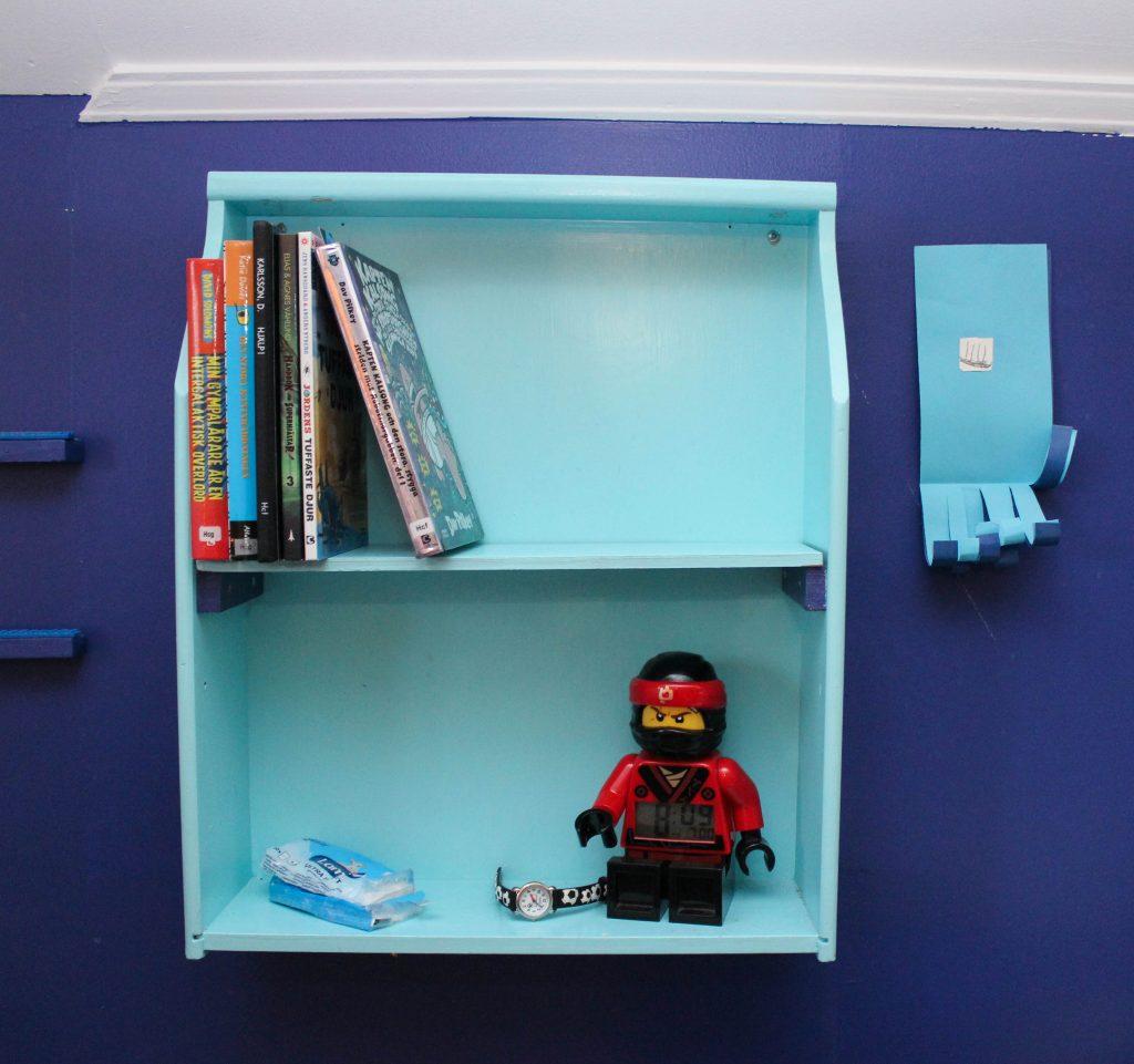 Hylla i två våningsplan målad turkosblå med böcker och len legoväckarklocka.