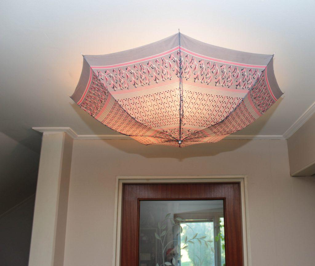 Ett rosa och grått parapaly hänger med regnsidan nedåt i ett tak. Ett enkelt sätt att skapa unika lampor till ditt hus.