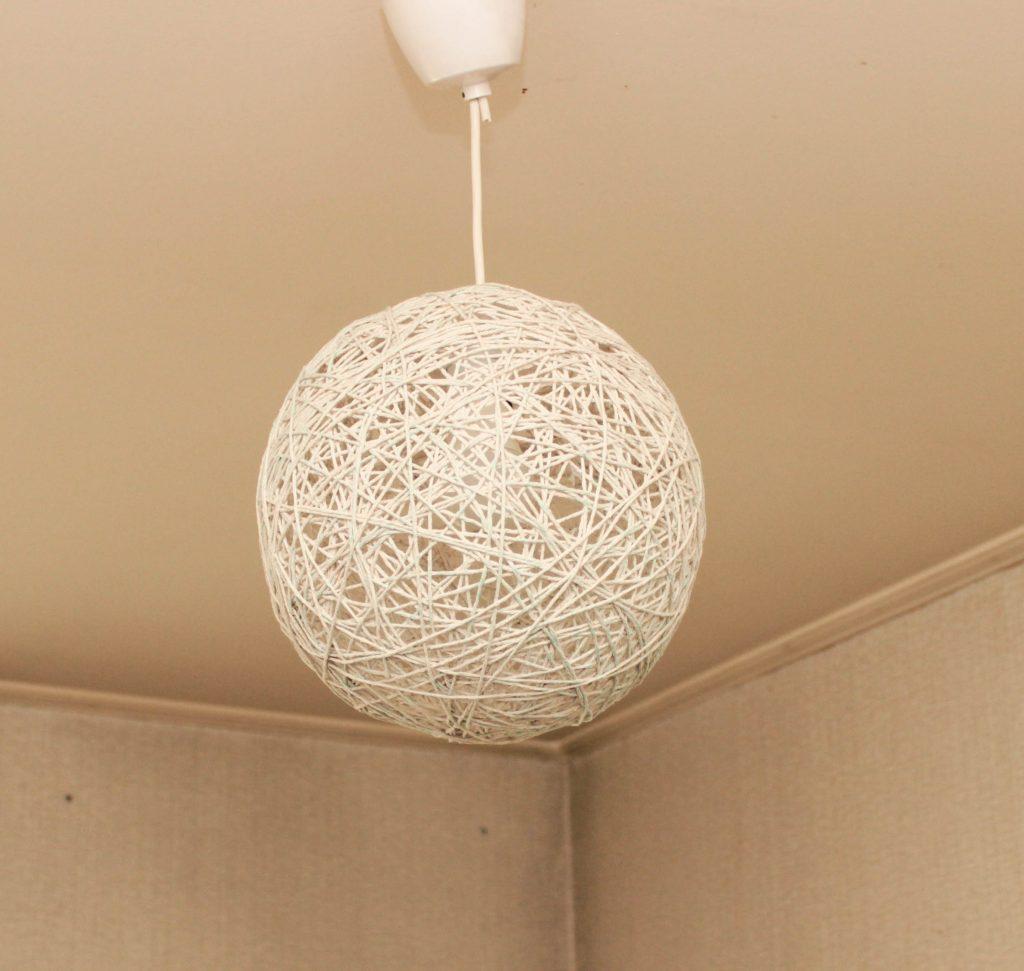 En snörboll hänger i taket och skapar en fin lampa.