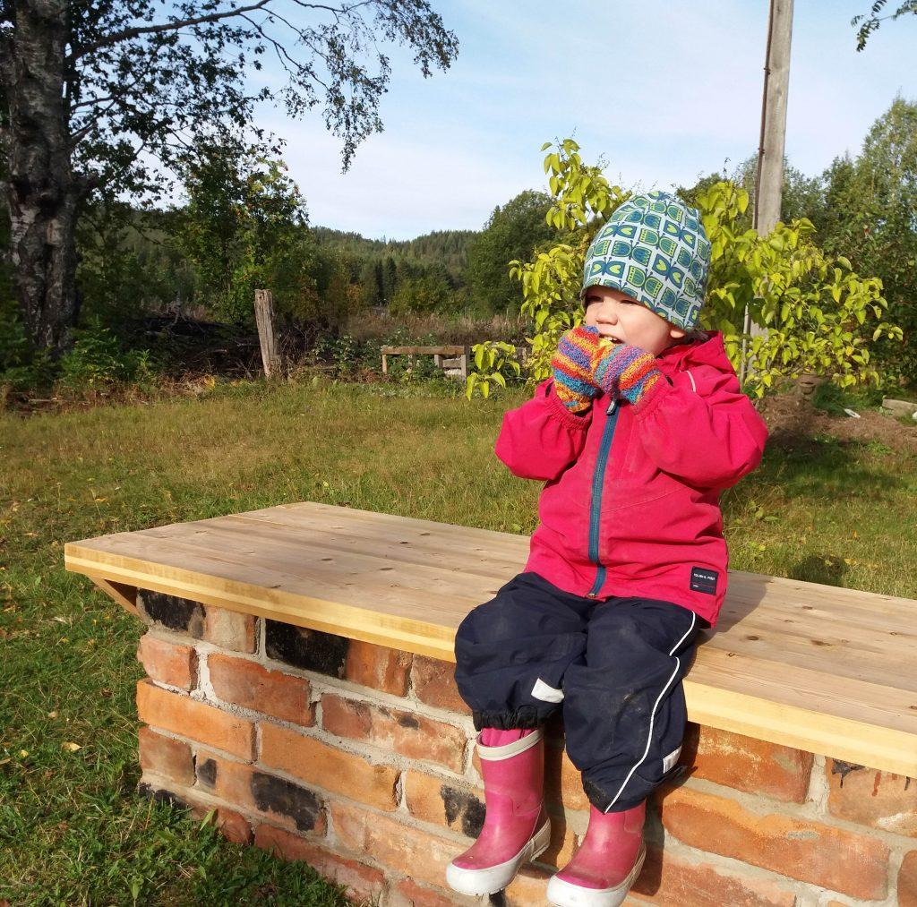 Barn som sitter på trädgårdsbänken och äter ett äpple.