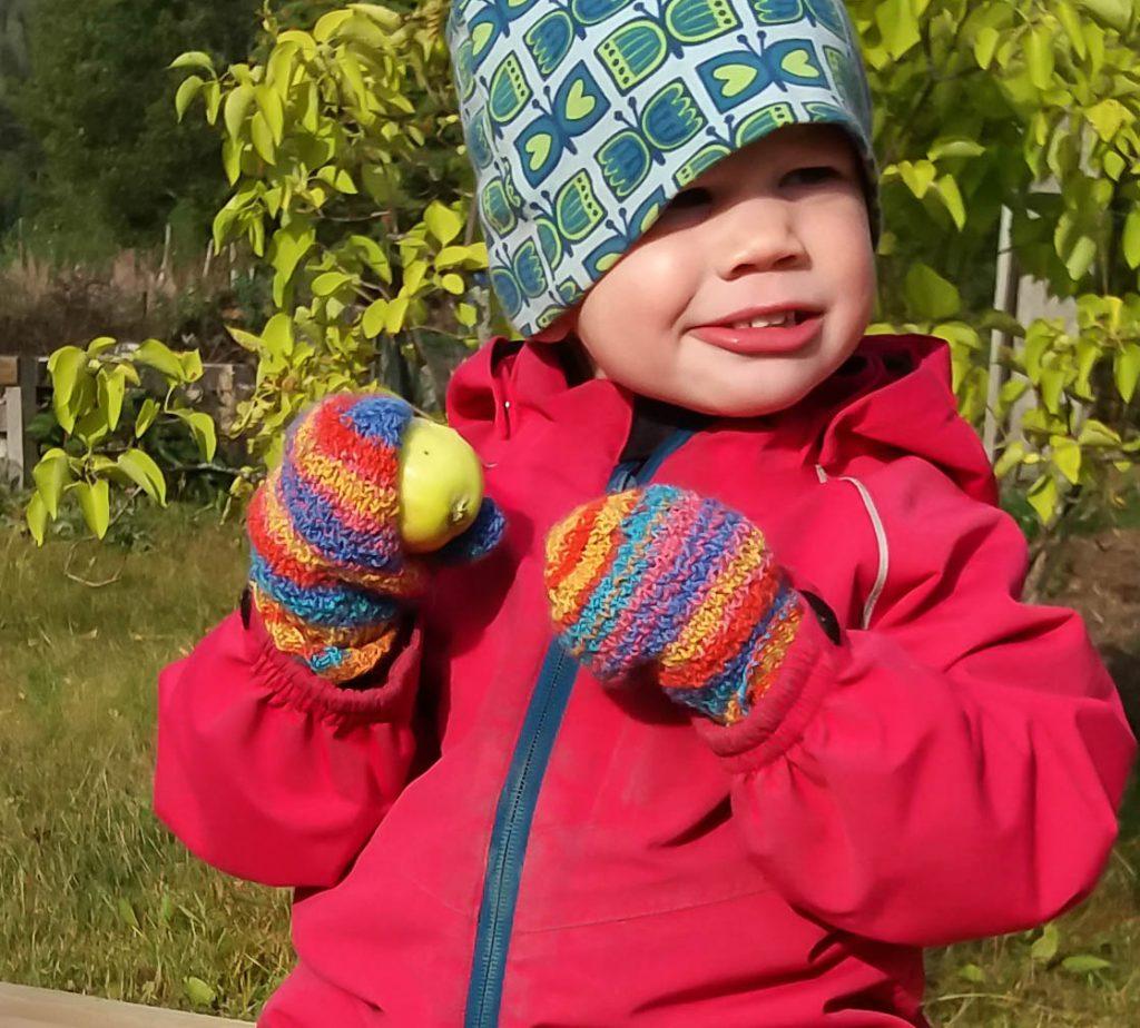 Barn som äter äpple och har på sig vantar av återbrukat garn.