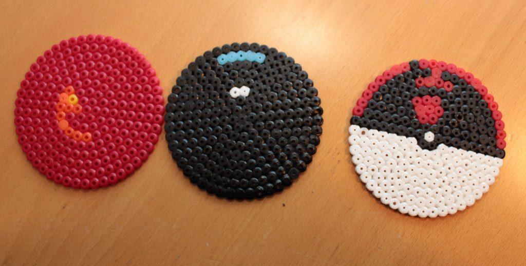 3 runda pärlplattor. En röd, en svart och en pokeboll.