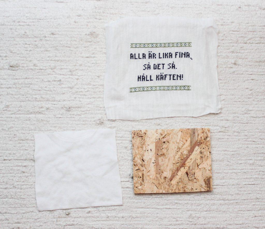 Vad du behöver för att montera på en bit trä: Broderi, vitt tyg, träbit och pins.