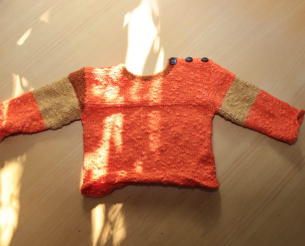 Stickad, orangea tröja.