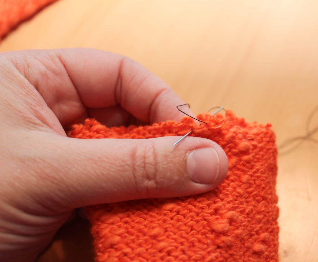Närbild på hand som syr stygn i varje ögla.