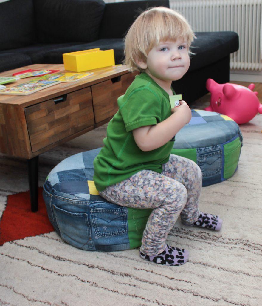 Två sittpuffar av jeans i ett vardagsrum med en tvååring som sitter på.